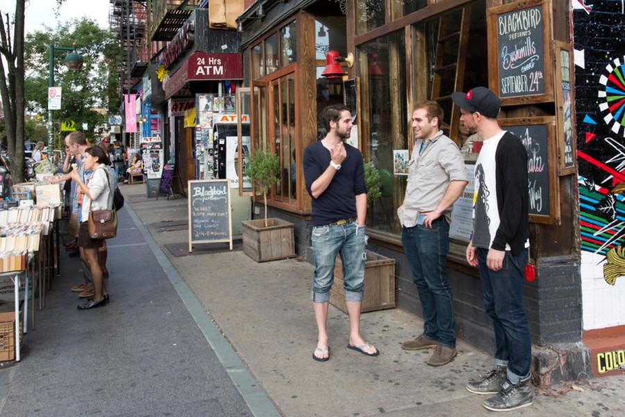 white men talking on city corner
